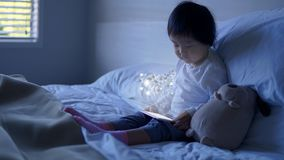 Small Asian chinese toddler sitting on the bed with special effects from ipad royalty free stock photography