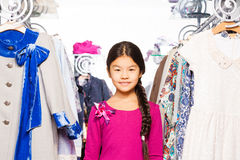 Small Asian girl with braid stands between clothes Stock Image