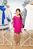 Small Asian girl with standing between clothes Royalty Free Stock Photography