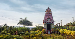 Small asian temple. Ancient small temple against trees and bushes, India Royalty Free Stock Photos