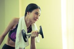 Small Asian woman lifting dumbbell in fitness Royalty Free Stock Image