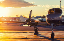 Small Aviation: Private Jet is Parked on a Tarmac in a Beautiful. Sunset Light stock photo