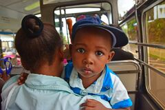 A cute yet curious little Rodriguan baby being carried by his mother in a public bus in Rodrigues Island, Mauritius