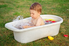 A small baby bathed in the bath and playing Stock Photography