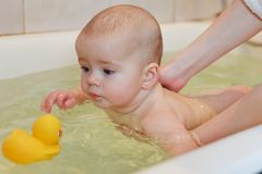 Small baby bathing. In the bathroom on mother hands Stock Photography
