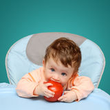 Small baby biting tomato Royalty Free Stock Images