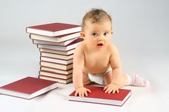Small baby and books. Small baby girl and many red books with red cover Royalty Free Stock Photography