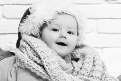 Small baby boy with adorable curious face in yellow sweater laying on tummy in new year hat and knitted scarf on white stock image