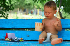 Small baby boy drinking coffee with chocolate. Morning ritual, small baby boy sitting on blue rural bench drinking coffee with chocolate Stock Photography