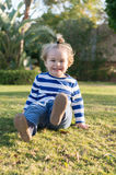 Small baby boy with happy face on green grass barefoot Royalty Free Stock Image