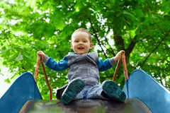 Small baby boy having fun on slide in spring park Stock Images