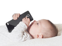 Small baby boy holding smartphone in bed Royalty Free Stock Images