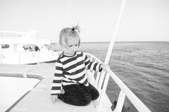 Small baby boy sailor, captain of yacht in marine shirt. Small baby boy sailor or cute child captain of yacht, boat or ship white color with blonde hair in stock photo