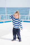 Small baby boy sailor, captain of yacht in marine shirt. Traveling, vacation. small baby boy sailor or cute child captain of yacht, boat or ship white color with Royalty Free Stock Image