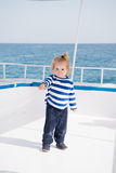 Small baby boy sailor, captain of yacht in marine shirt. Traveling, vacation. small baby boy sailor or cute child captain of yacht, boat or ship white color with Stock Photography
