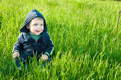 Small baby boy sitting in the grass Royalty Free Stock Photo