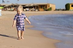 Small baby boy walking the seaside. oncept for travel ad. copy space.  stock photo