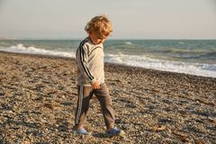 Small baby boy walking the seaside. the boy walks at sunset on the beach royalty free stock image