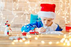 Small baby boy writes a list of gifts stock photos