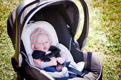 Small Baby in Car Seat. A happy baby boy sitting in a car seat with bright blue eyes cooing Stock Photo
