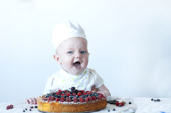 Small baby confectioner. Funny newborn confectioner with berry biscuit cake Royalty Free Stock Photography