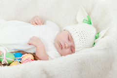 Small baby dressed in Easter bunny cap with eggs Stock Image
