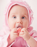 Small baby with a dummy. Small baby with a pink dummy on white background Royalty Free Stock Photo