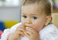 Small baby eating apple stock photo