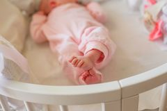 Small baby feet clad in pink romper. Tiny fingers of the newborn. The child has crossed legs and lies in a round white bed stock images