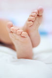 Small baby feet in soft selective focus. White and blue background Stock Photo