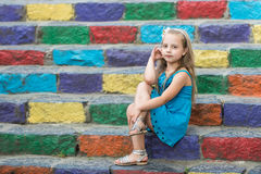 Small baby girl in blue dress on colorful stairs. Small baby girl or cute child with adorable face and bow in blonde hair in blue dress outdoor sitting on stock photography