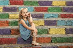 Small baby girl in blue dress on colorful stairs. Small baby girl or cute child with adorable face and bow in blonde hair in blue dress outdoor sitting on royalty free stock photos