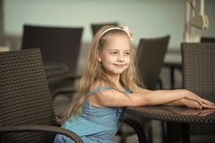 Small smiling baby girl in blue dress near cafe table. Small baby girl or cute happy child with adorable smiling face and bow in blonde hair in blue dress royalty free stock photo