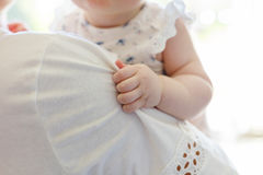 Small baby girl holding the hand on mother's shoulder Royalty Free Stock Image