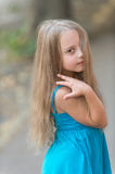 Small baby girl with long hair in blue dress outdoor Royalty Free Stock Photos