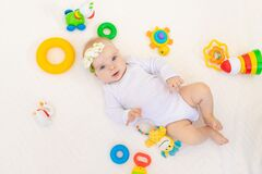 Small baby girl 6 months old lying on her back on a white bed at home among toys, top view