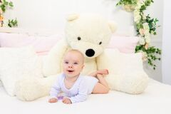 A small baby girl 6 months old is lying on a white bed at home with a large Teddy bear