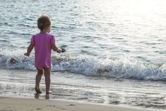 Small baby girl playing in the waters edge on the beach royalty free stock photos