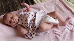 Small baby girl in pretty dress lies on blanket stock video