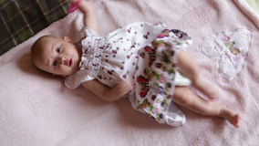 Small baby girl in pretty dress lies on blanket stock footage