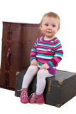 Small baby girl sitting on the old wooden box with a suitcase, w Stock Images