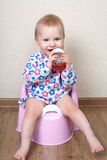 Small baby girl, is sitting on a pink pot and drinks water Stock Photos