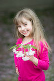 Small baby girl with smiling face holding pink sakura blossom. Small baby girl or cute child with adorable smiling face and blonde hair in pink shirt holding Royalty Free Stock Photography