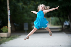 Small baby girl with smiling face jumping in blue dress Stock Photo