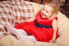 Small baby girl smiling and proud as she sits in an adult sized leather recliner chair. Royalty Free Stock Images