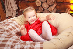 Small baby girl smiling and proud as she sits in an adult sized leather recliner chair. Royalty Free Stock Photos