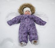 Small baby girl in the snow. Winter Cold First Happy New Year Merry Christmas Forest White Stock Photo