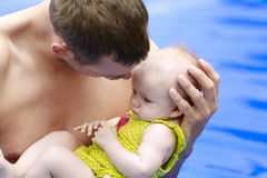 Small baby girl is swimming in the pool with daddy Royalty Free Stock Photos