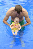 Small baby girl is swimming in the pool with daddy Stock Image