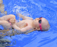 Small baby girl is swimming in the pool Royalty Free Stock Photography